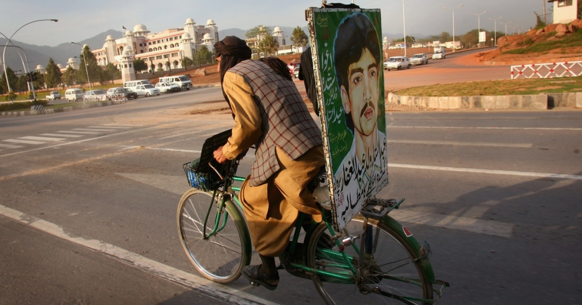 A Pakistani man rides his bicycle adorned with a portrait of his missing son who was abducted by Pakistani intelligence agents, in Islamabad on March 30,2007.</p>