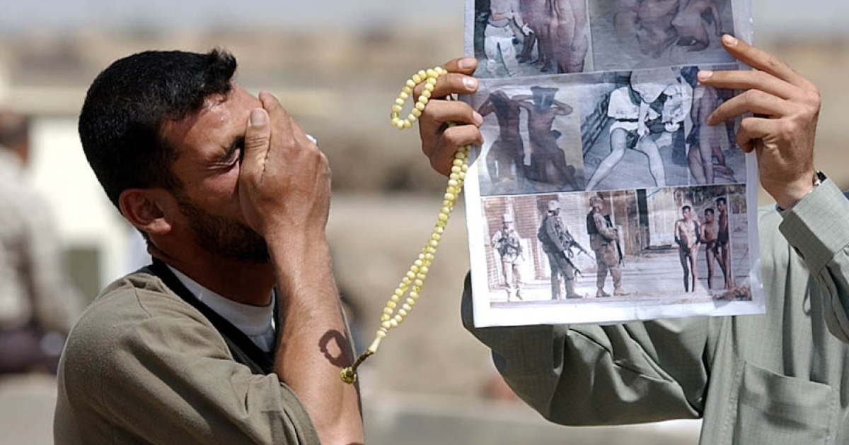 A relative of an Iraqi prisoner being held by U.S. authorities at the Abu Ghraib prison reacts to a newspaper featuring photos of U.S. soldiers abusing Iraqi prisoners inside the detention center on May 8, 2004. Before the fall of Saddam Hussein, the prison was notorious for torture and executions. After 2004, images were made public of Iraqi detainees being beaten and sexually humiliated at the prison.</p>