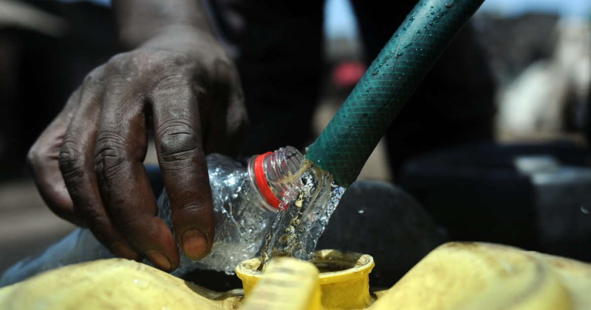 A water vendor collects water in jerrycans to sell in Nairobi's Mathare slum on Mar. 22, 2012.</p>