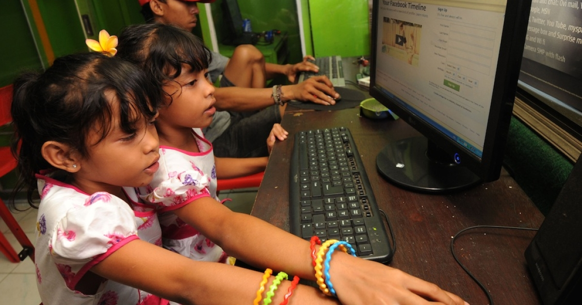 In this photograph taken February 2, 2012, Indonesian children log onto a Facebook page at an internet shop on the resort island of Bali.</p>
