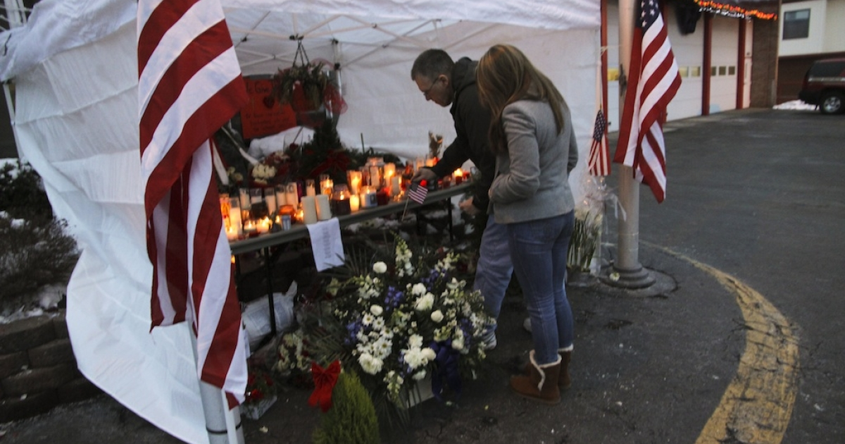 Mourners place an American flag at a makeshift memorial at the West Webster Fire Station on December 26.</p>