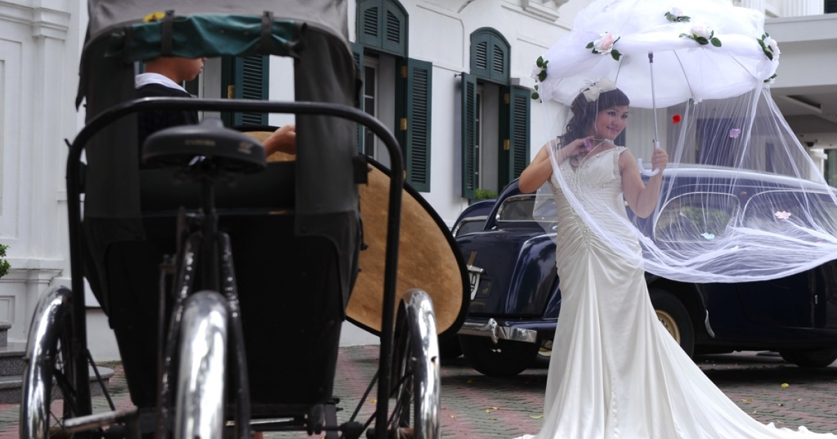 A bride poses for a wedding photo album in front of a colonial style hotel, rickshaw and old cars in downtown Hanoi.</p>