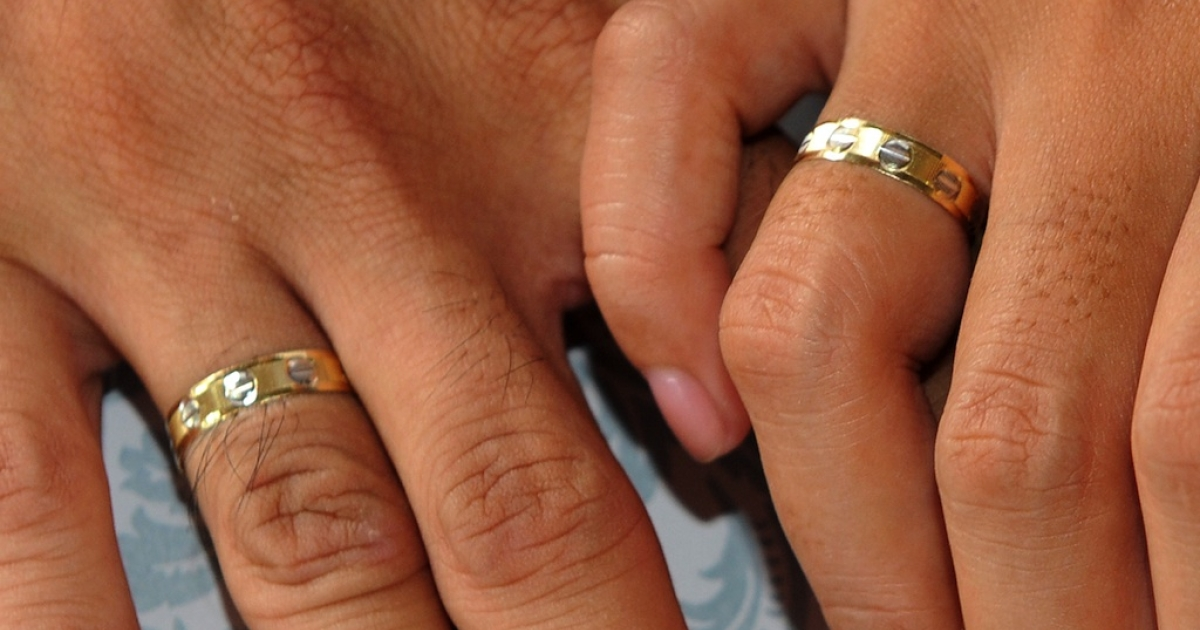 A couple holds hands showing their wedding rings.</p>