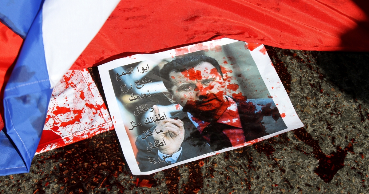 A picture of Syria's embattled President Bashar al-Assad sprayed with red paint lies on the ground next to a Russian flag about to be set on fire by protesters opposed to the Syrian regime during a demonstration outside the Russian embassy in Beirut on February 5, 2012 against a second veto by Moscow and Beijing on a UN Security Council resolution on the Syrian regime's bloody crackdown on dissent.</p>