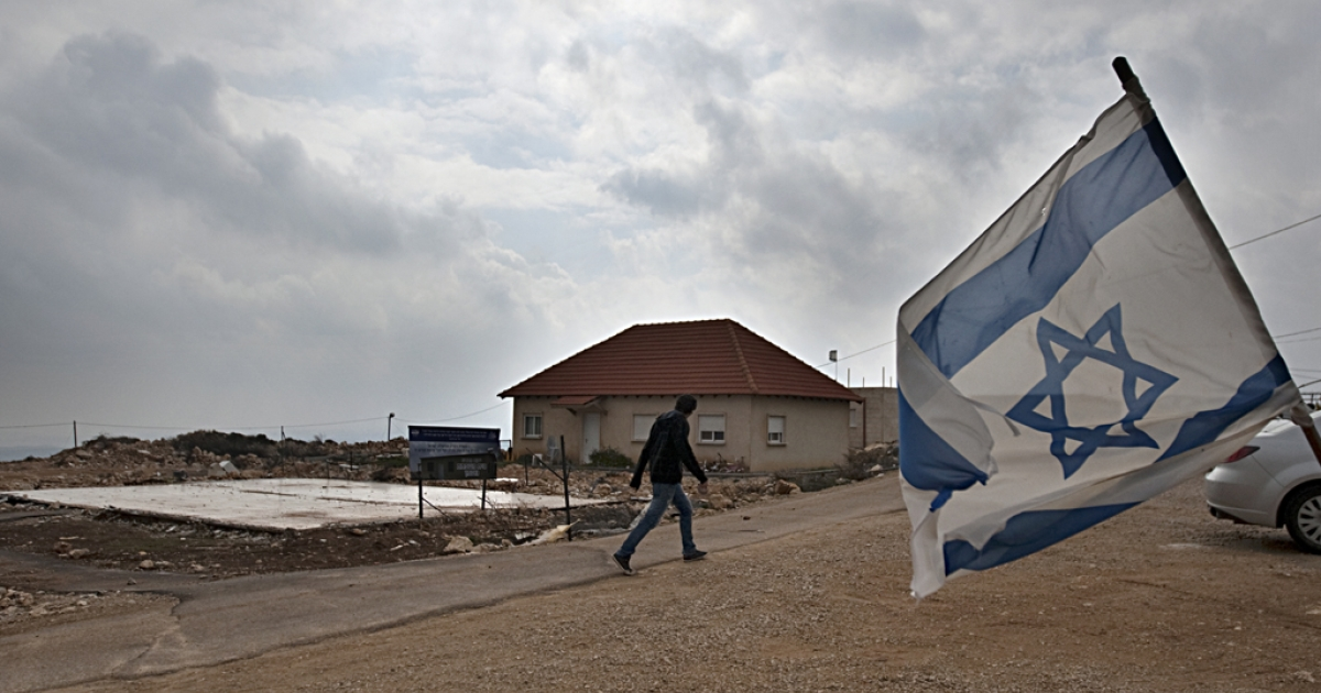 An Israeli flag flies in the wind as a Jewish settler walks past the remaining foundations of a demolished house, in the unauthorized West Bank settlement of Migron. Settlers have agreed to leave the oldest and largest settlement in the West Bank, as part of a deal with the Israeli government on March 11, 2012.</p>