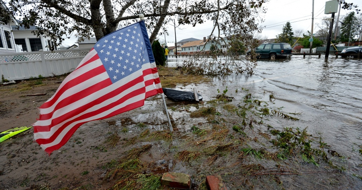An American flag flies from the front yard of a house in a flood damaged area October 30, 2012 in the Breezy Point area of Queens in New York that was hit hard by Hurricane Sandy.</p>