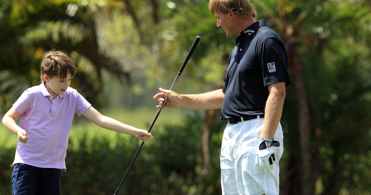 Ernie Els of South Africa with his son Ben who suffers from autism during the Els for Autism Pro-am at the PGA National Golf Club in West Palm Beach, Fla., on Mar. 12, 2012.</p>