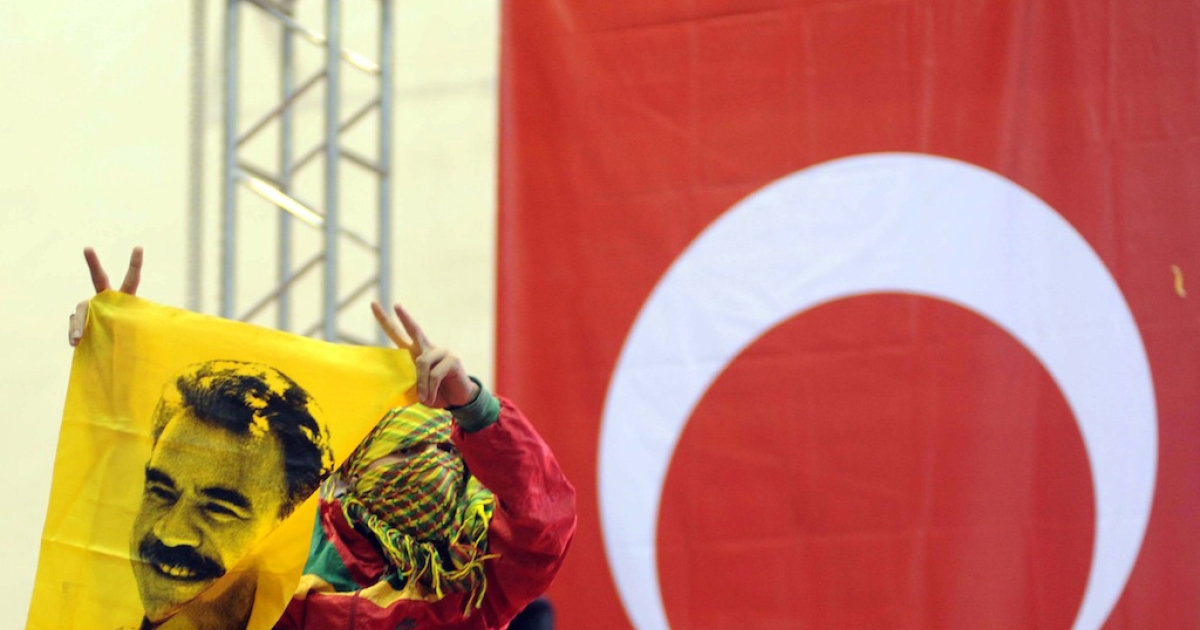 A supporter of the pro-Kurdish Peace and Democracy Party holds a poster of Abdullah Ocalan, the jailed leader of outlawed Kurdistan Workers Party, during the party's congress in Ankara on Oct. 14, 2012.</p>