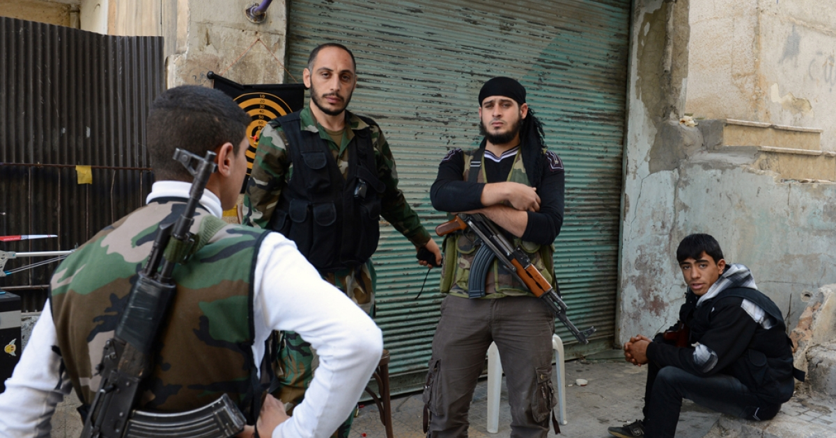 Syrian rebel fighters stand guard at a check point in Aleppo's northern Izaa quarter, on November 3, 2012.</p>