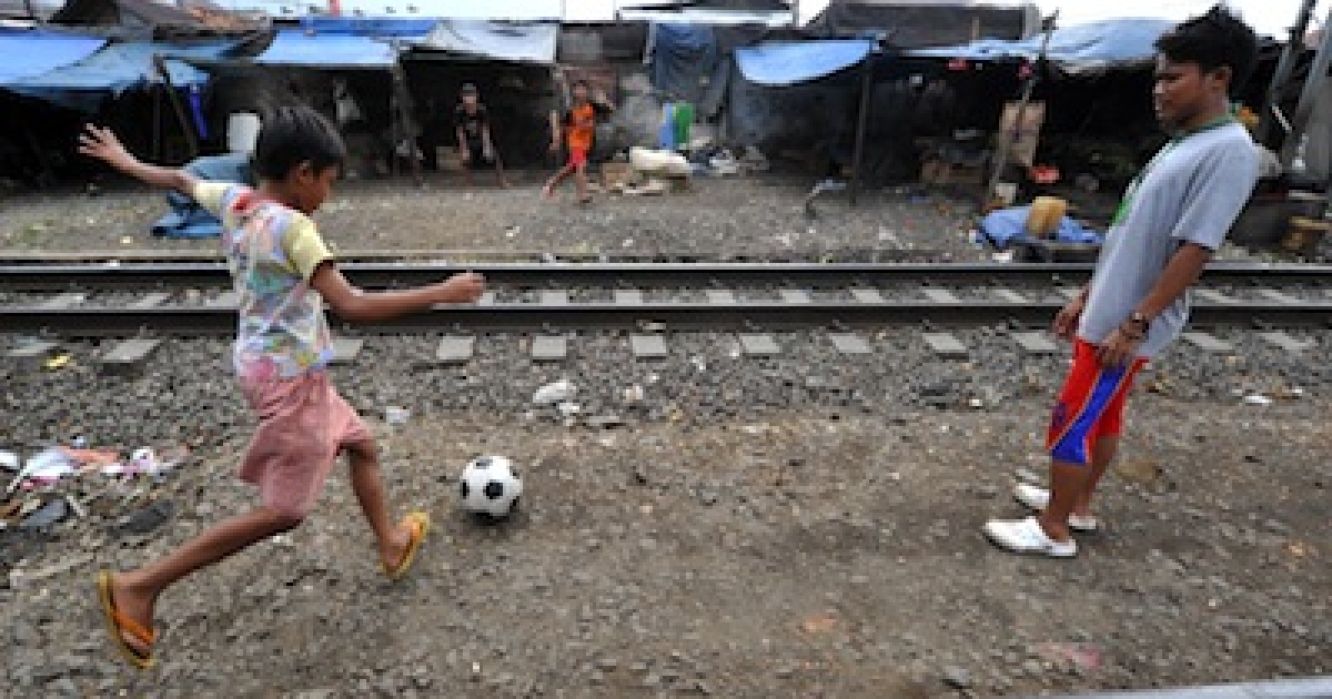 Indonesian boys practice football skills in the space between railway tracks in Jakarta on February 16, 2011.</p>