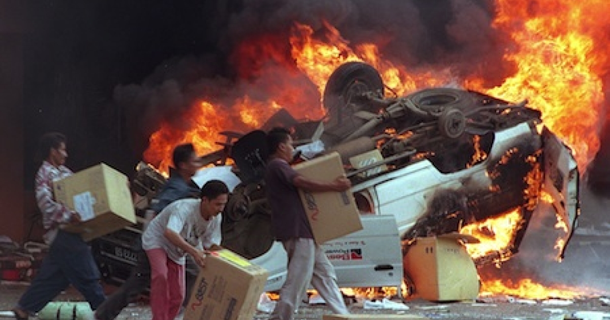 Angry Indonesian mobs burn cars as they plundered shops in Jakarta during 1998 street violence, which brought terror to the Indonesian capital.</p>