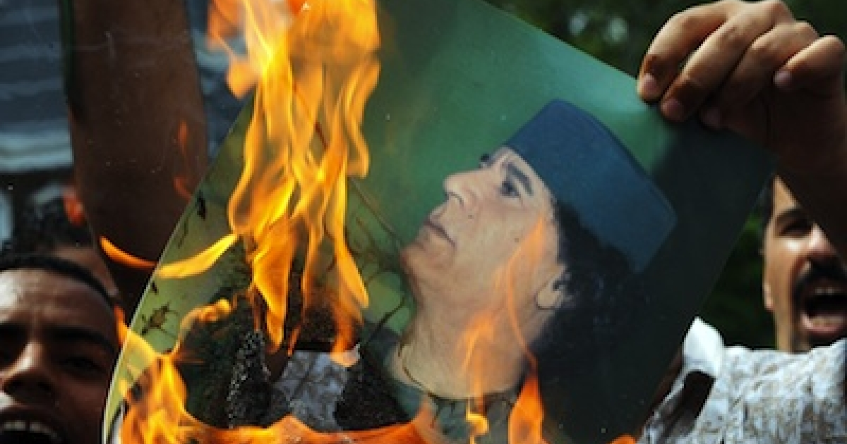 A Libyan protester burns a portrait of Libyan leader Moamer Kadhafi in front of the Libyan embassy in Kuala Lumpur, Malaysia, on February 23, 2011.</p>
