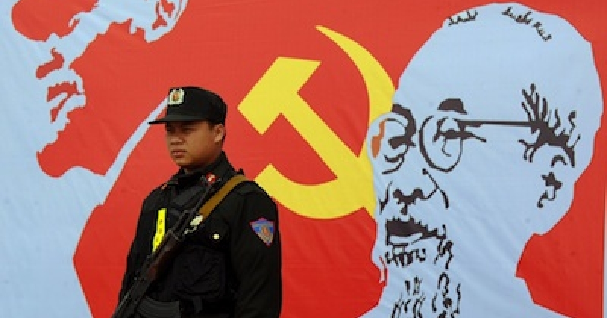 An armed policeman stands guard next to a portrait of late president Ho Chi Minh (R), founder of today's communist Vietnam, and Russian communist leader Vladimir Lenin (L), outside the venue of the current 11th national congress of the Vietnam Communist Party (VCP) in Hanoi on January 17, 2011. Vietnam's ruling communists met on January 17 to choose a new batch of leaders who are expected to oversee a drive to modernise the economy while refusing to abandon the country's authoritarian political system.</p>