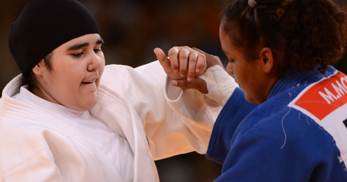 Saudi Arabia's Wojdan Shaherkani (white) competes with Puerto Rico's Melissa Mojica (blue) during their women's +78kg judo contest match of the London 2012 Olympic Games on August 3, 2012 at the ExCel arena in London.</p>