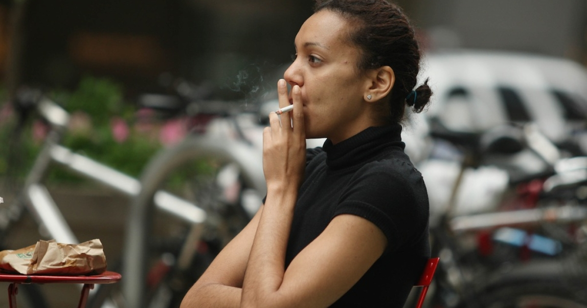A woman smokes a cigarette in the pedestrian thoroughfare located in Times Square May 23, 2011 in New York City. A new study has found that quitting smoking by 30 almost eliminates early death risk.</p>