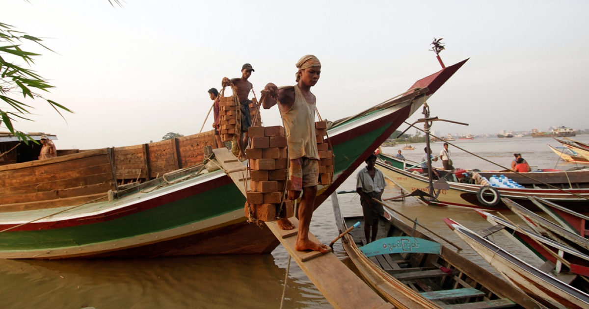 This picture shows workers carrying bricks with bamboo framework from a boat at the harbor in Yangon. The World Bank announced on April 26, 2012 that it would open an office in Myanmar, nearly two decades after its last projects in the country.</p>