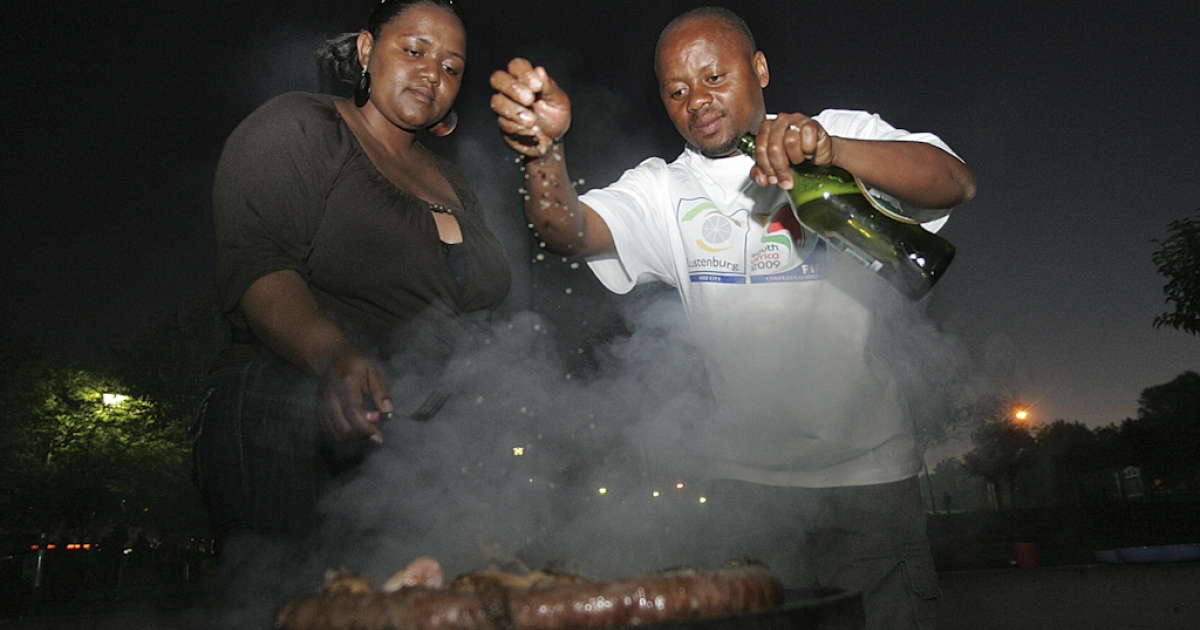 South Africans gestures around a braai, barbecue in Afrikaans, in Soweto on September 19, 2009. Part cooking method, part national obsession, the braai is a shared social custom that cuts across race and social divisions 15 years after the fall of white minority rule.</p>