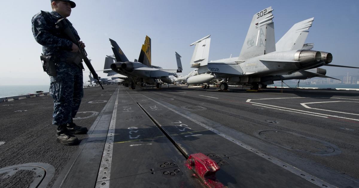 A US Navy serviceman holding a machine gun stands near F/A-18 Hornet warplanes on the flight deck of the USS Carl Vinson,</p>