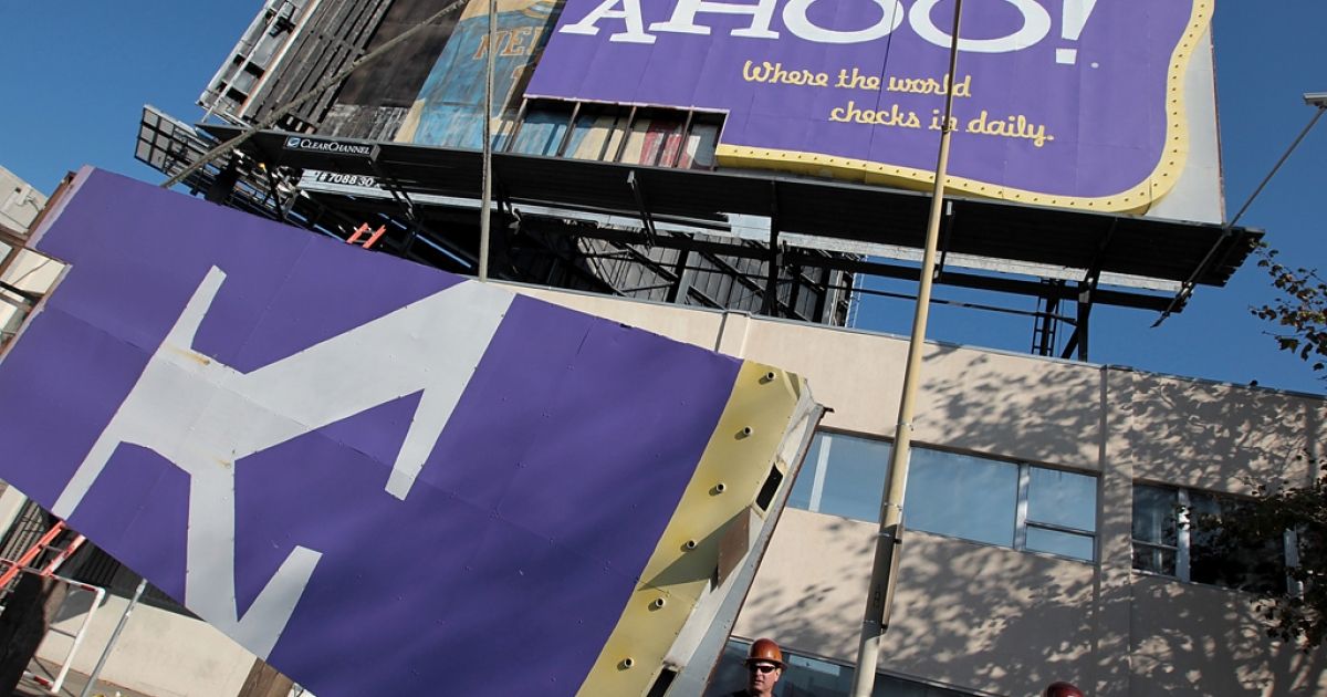 A worker moves a section of a Yahoo! billboard onto a truck in San Francisco, California. The company has seen its first resignation in the wake of the scandal over CEO Scott Thompson's botched academic record: board director Patti Hart.</p>