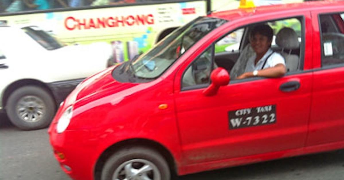 One of many Chery cars from China makes its way down a crowded street in Yangon.</p>