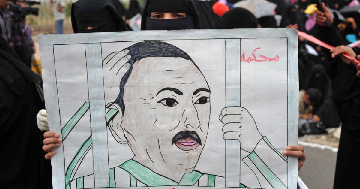 A Yemeni anti-government protester holds a drawing calling for the trial of President Ali Abdullah Saleh.</p>