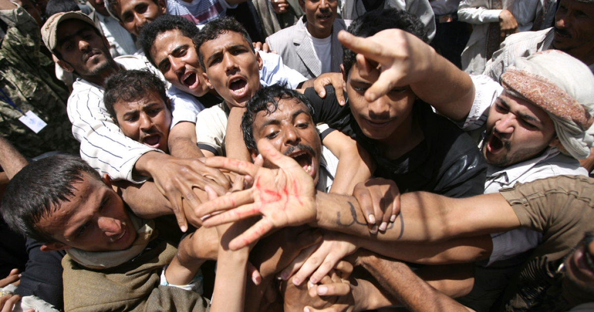 Yemeni protesters shout slogans and show a palm with writing in Arabic that reads,