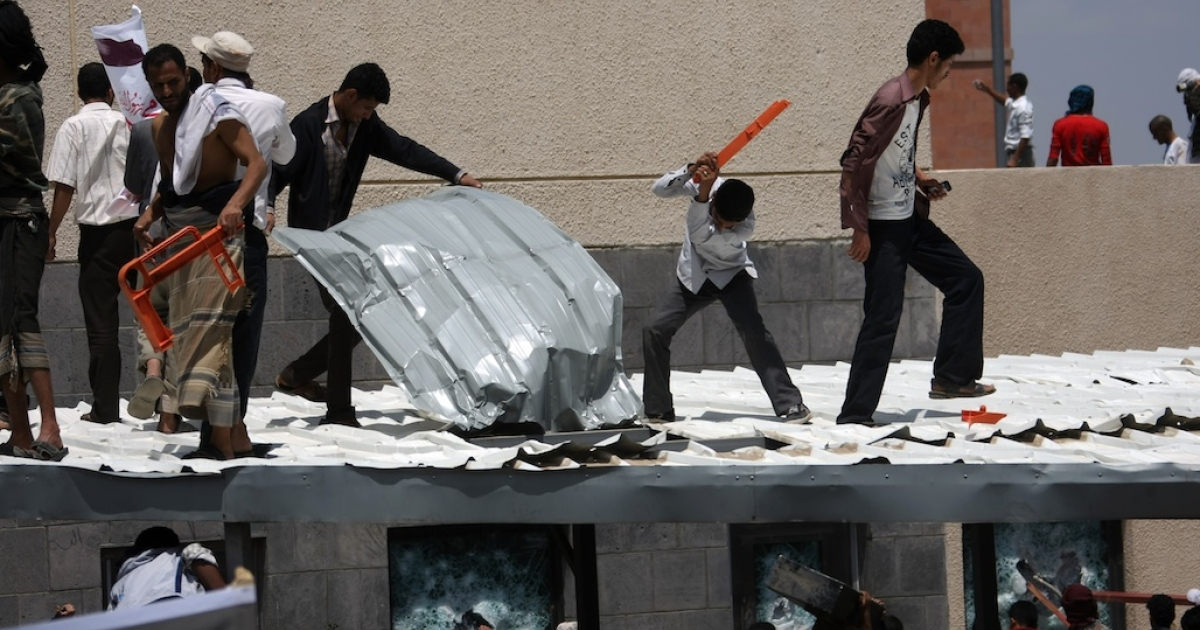Yemeni protesters try to break through the US embassy in Sanaa during a protest on Sept. 13, 2012. Yemeni forces managed to drive out angry protesters who stormed the embassy in the Yemeni capital, with police firing warning shots to disperse thousands of people as they approached the main gate of the mission.</p>