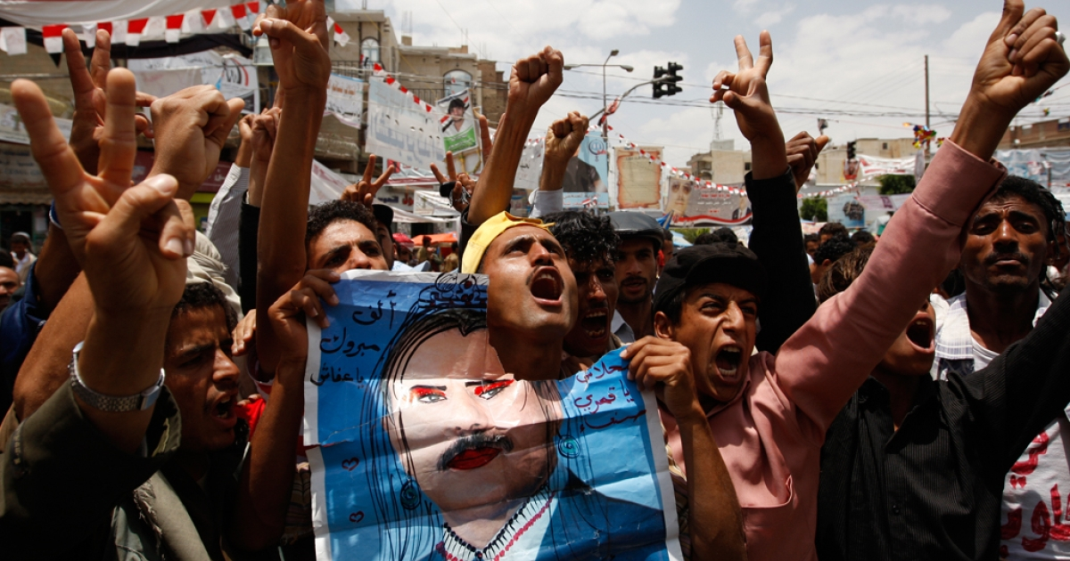 Yemeni anti-government protesters shout slogans during a demonstration calling for the ouster of President Ali Abdullah Saleh (defaced poster) in Sanaa on June 4, 2011.</p>