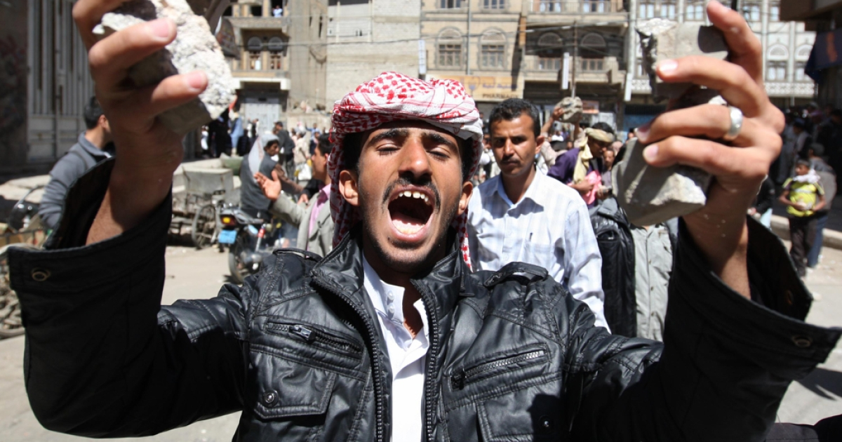 a Yemeni anti-government protester shouts slogans calling for the ouster of President Ali Abdullah Saleh as he holds stones in his hands during clashes with regime loyalists in central Sanaa on Feb. 17, 2011.</p>
