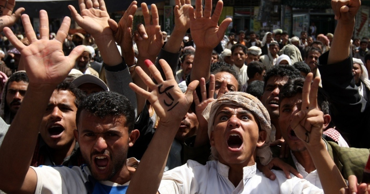 Tens of thousands of anti-government Yemeni mourners chant slogans as they gather next to the bodies of activists who were among more than 50 protesters gunned down by snipers in Sanaa on March 20, 2011 during a mass funeral procession in the capital.</p>