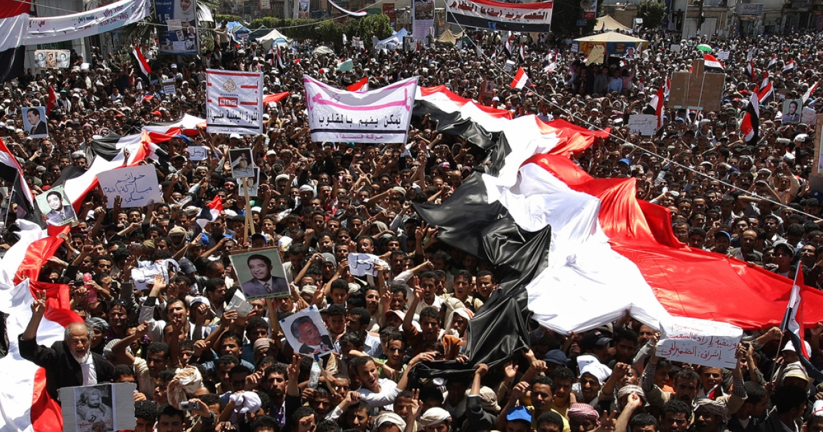 Yemeni protesters hold their national flag during a massive anti-regime rally in the capital Sanaa on March 1, 2011.</p>