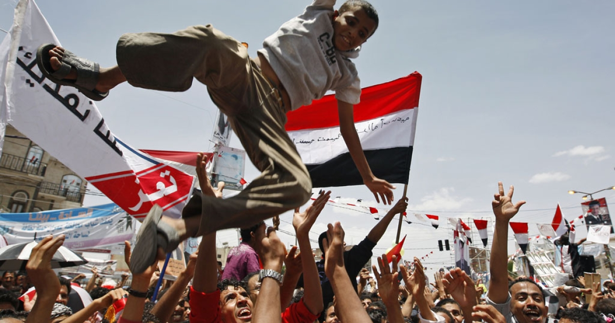 Yemeni anti-government protesters throw a youth in the air as they gather in Sanaa on June 5, 2011 to celebrate what they said was the fall of Yemen's regime.</p>