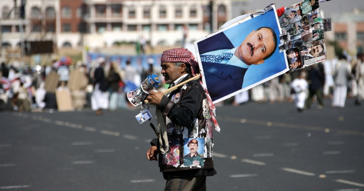 A Yemeni supporter of President Ali Abdullah Saleh wears and carries portraits of the embattled leader during a pro-regime rally on Dec. 2, 2011.</p>