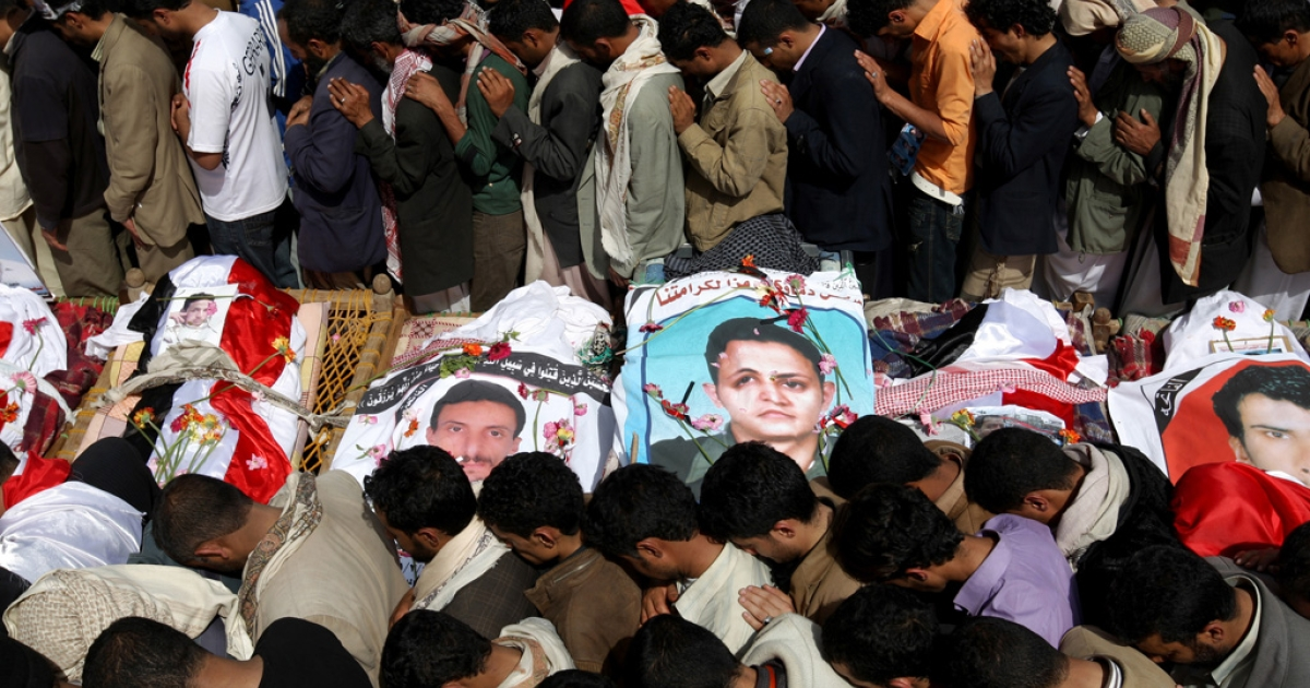 Anti-government Yemeni mourners pray over the bodies of activists who were among more than 50 protesters gunned down two days ago by snipers in Sanaa on March 20, 2011 during a mass funeral procession in the capital.</p>