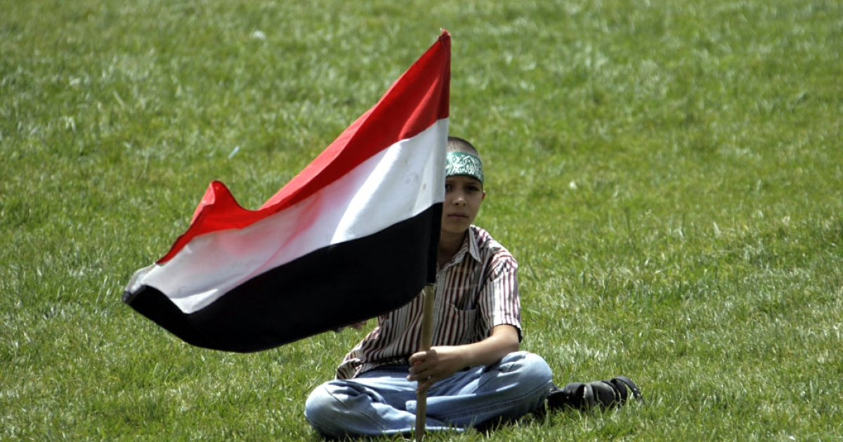 A Yemeni youth holds the national flag as he readies to join other supporters of Yemen's President Ali Abdullah Saleh in a protest in support of his regime following Friday noon prayers in the capital Sanaa, on Aug. 26, 2011.</p>