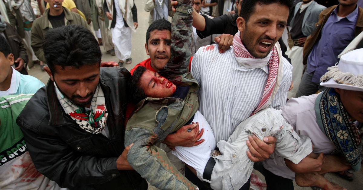 Yemeni anti-government protesters carry away a wounded demonstrator in Sanaa March 18, 2011 as more than 30 anti-regime protesters were shot dead and over 100 wounded, medics and witnesses said.</p>