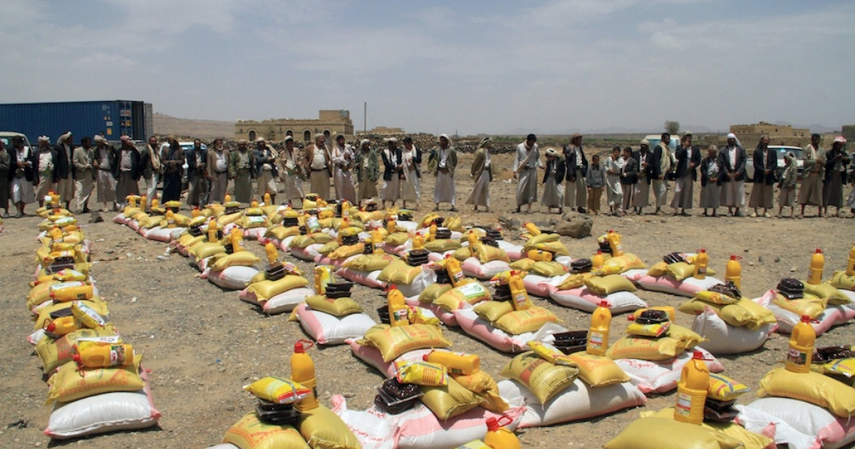 Yemeni men wait to collect food aid donated by a Kuwaiti charity laid out for internally displaced families living in a district of the Yemeni capital Sanaa, on July 19, 2012.</p>