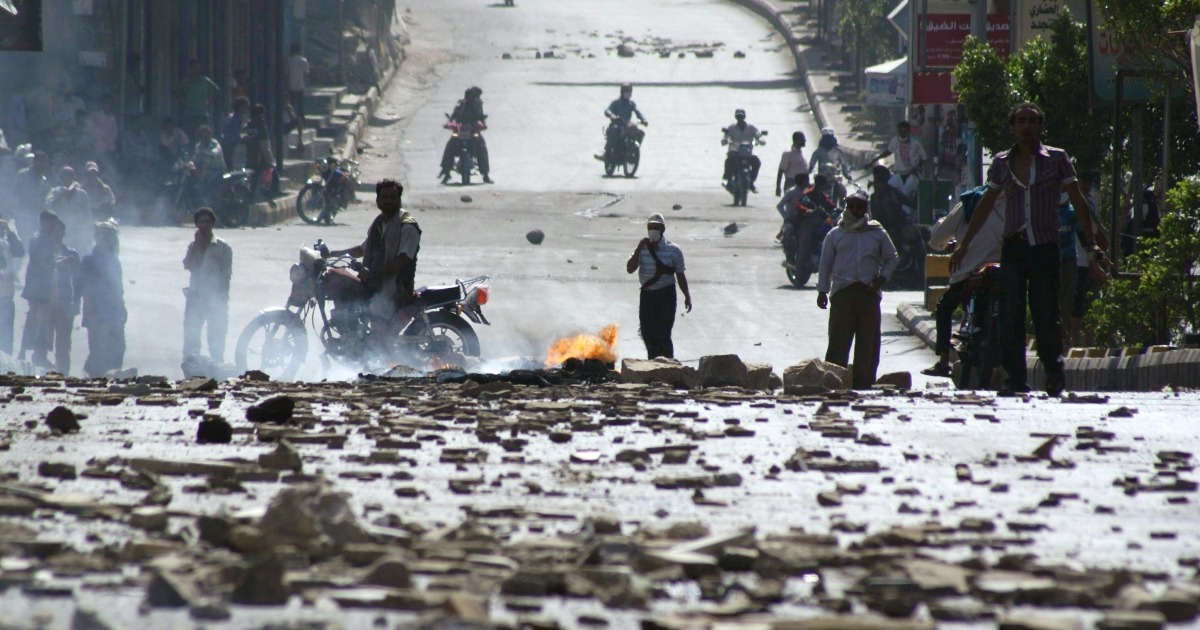 Yemenis stand near damages caused during heavy riots in Taiz, south of the capital Sanaa, on April 4, 2011 after Yemeni security forces shot dead 17 anti-regime demonstrators and wounded scores more, on the second day of lethal clashes in the city.</p>