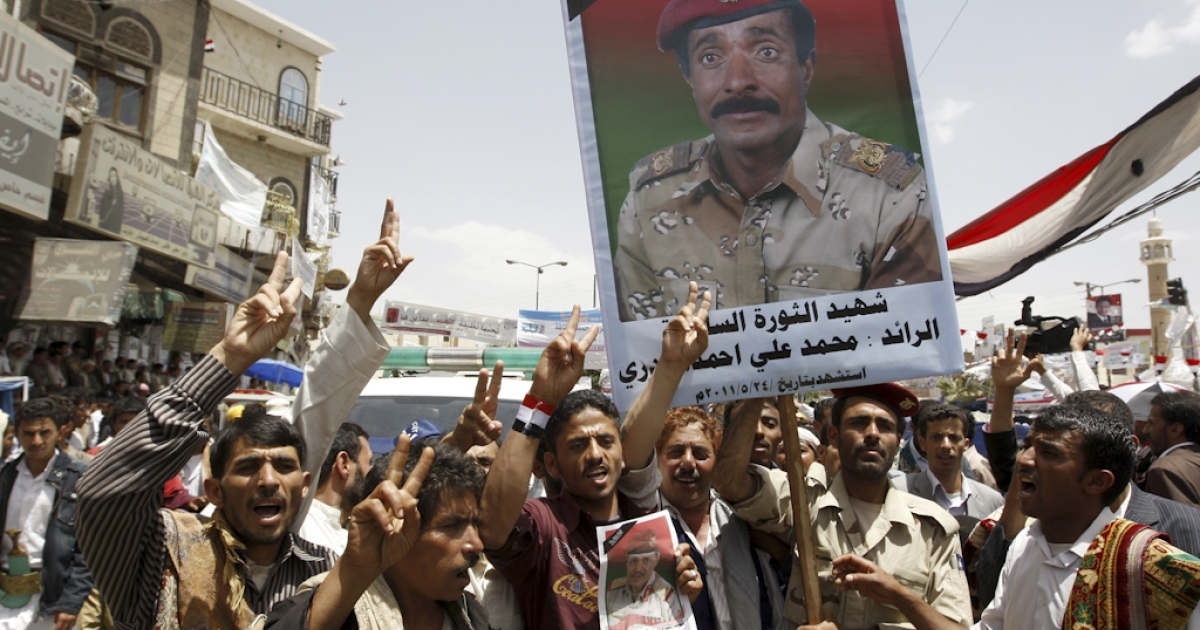 Anti-government protesters shout slogans as they hold up an image of a killed soldier during a demonstration calling for the ouster of President Ali Abdullah Saleh in Sanaa on May 29, 2011, as dissident Yemeni generals accused the embattled president of surrendering the southern province of Abyan to 'terrorists' and called for more troops to defect.</p>