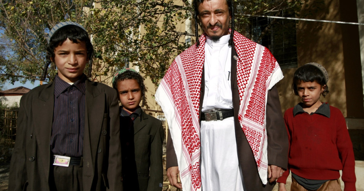 Yemeni Jewish Rabbi Yahia Yussef Mussa (C), sporting a chequerred Keffiya, poses for a picture with unidentified young relatives outside his apartment in the Yemeni capital Sanaa. The community, which numbered tens of thousands in the first half of the 20th century, has moved gradually over the past 50 years to Israel, the United States or the United Kingdom with the main exodus taking place between 1949 and 1952, following the creation of the Jewish state in 1948.  (AHMAD GHARABLI/AFP/Getty Images)</p>