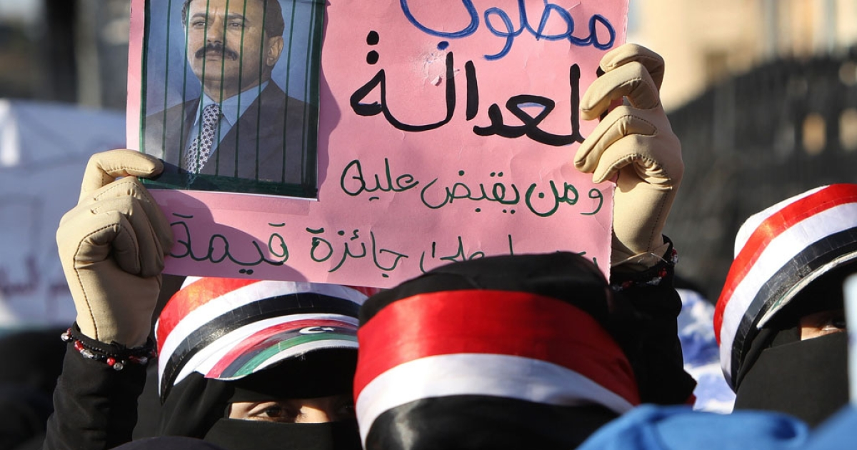 A Yemeni woman holds a sign bearing a doctored picture of  President Ali Abdullah Saleh behnid bars with Arabic writing which reads: