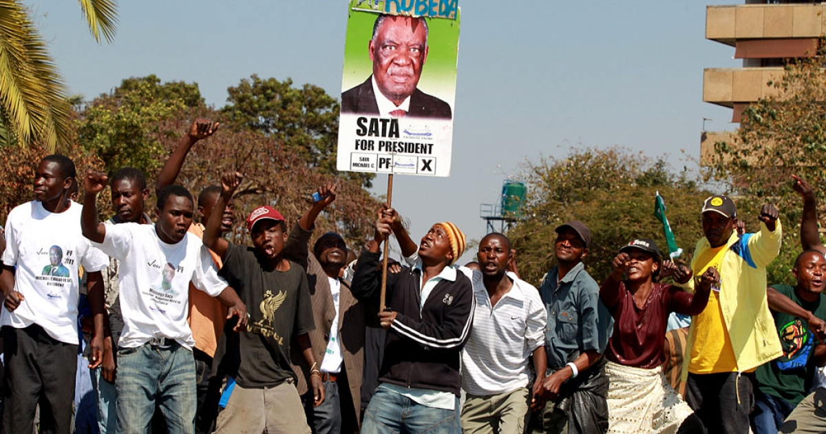 Opposition leader Michael Sata was announced the winner of presidential elections in Zambia early on Friday. Here his supporters of cheer and wave a placard with his picture on it during the election campaign.</p>