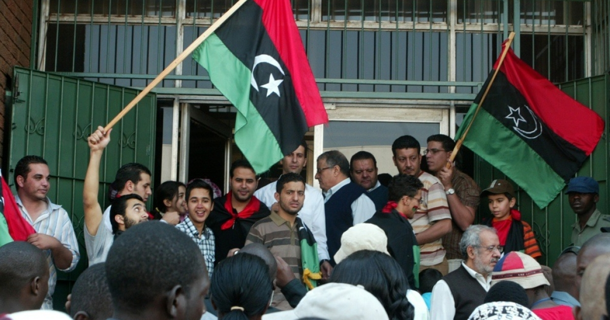 Libyan embassy staff and Libyan nationals demonstrate outside the Libyan embassy in Harare on August 24, 2011. Libya's ambassador to Zimbabwe led a demonstration in which Libyans burned portraits of embattled leader Moammar Gaddafi and replaced Gaddafi's green flag with the old tricolor red, black and green flag from independence in 1951. The Mugabe government has ordered the deportation of the Libyan ambassador and others for these actions.</p>