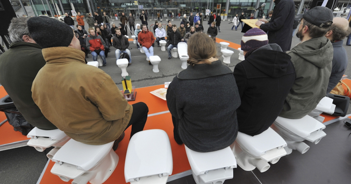 Participants from various sanitation and hygiene concerns address a press conference while sitting on toilets in front of Berlin's central railway station on November 19, 2008, on the occasion of World Toilet Day.  The UN has established that some 38 percent of the world's population are living without adequate sanitation, and has called on governments to reduce that number by half by 2015.</p>