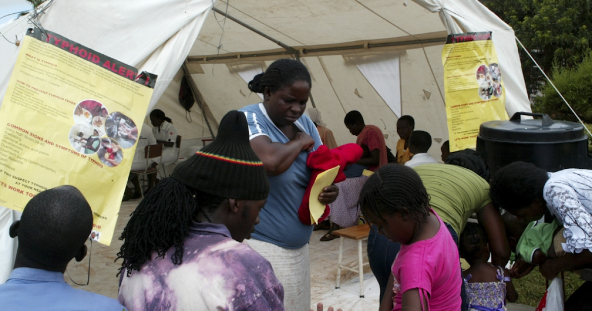 Patients receive medication at a typhoid screening and treatment centre setup in a temporary tent at a clinic in the Kuwadzana township, on January 24, 2012, in Harare, Zimbabwe. Doctors reported at least 800 cases in a typhoid outbreak in the Zimbabwean capital.</p>