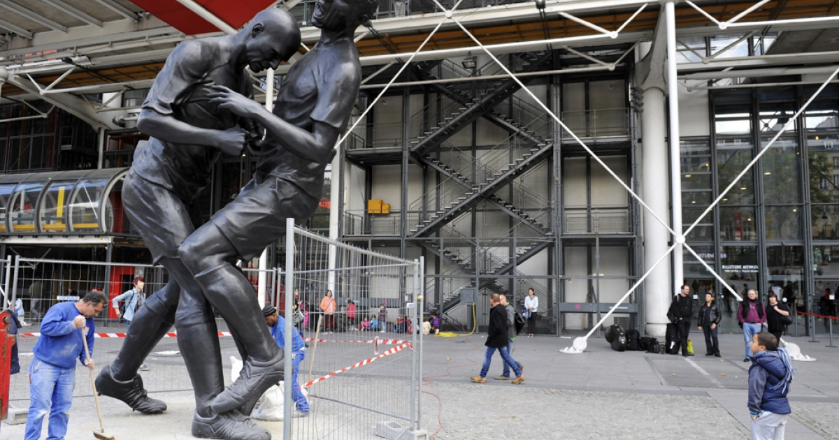 Employees sweep on September 26, 2012 in Paris near a bronze sculpture by Algerian artist Adel Abdessemed displayed in front of the Centre Pompidou modern art museum. The sculpture immortalizes Zinedine Zidane's headbutt against Italian player Marco Materazzi during the 2006 World Cup final. The Centre Pompidou will dedicate a retrospective to Abdessemed from October 3, 2012 to January 7, 2013.</p>