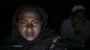 Salima, a Rohingya woman, talks to her husband, son and daughter, who are all being held by traffickers abroad, from an Internet hut in Thae Chaung village. She has to pay $600 and they discuss how to raise it.