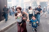 A mother and her children escape teargas fired by police on protesters in Beirut on Aug. 22, 2015.