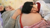 Li Yan, pregnant with her second child, lies on a bed as her daughter places her head on her mother's stomach in Hefei, Anhui province February 20, 2014.