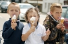 Children eat ice cream that's melting fast at the annual horse fair Appleby-in-Westmorland, Britain.